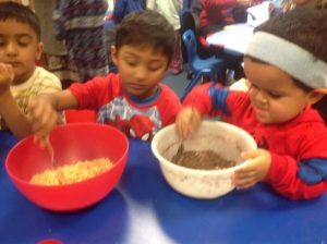 Making cakes was a great opportunity to share. One person spooned the krispies into the bowl whilst someone else stirred them in.
