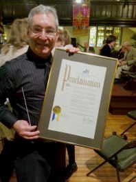 Music Director and orchestra founder Mike Tietz shows off the official proclamation.