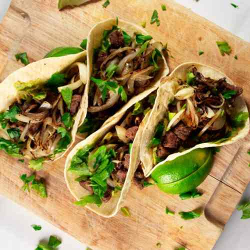 Marinated Beef Tacos served on wooden block