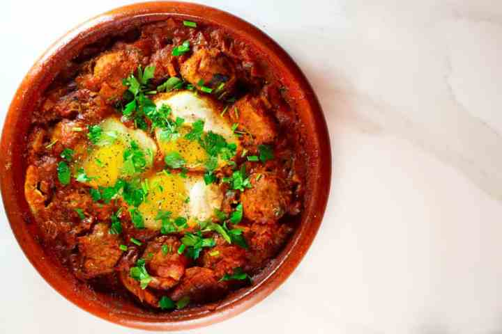 Eggs and kafta tagine garnished with parsley.