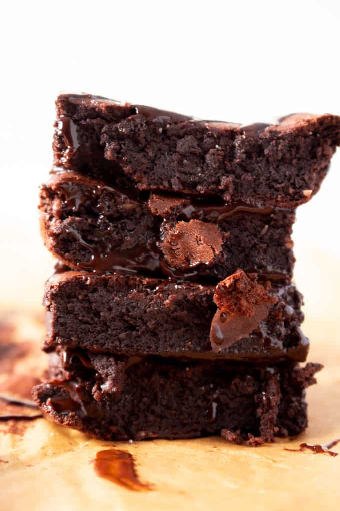 Paleo Brownies stacked on top of parchment paper