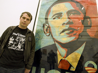"Artist Shepard Fairey poses beside his ""Obama HOPE"" image, part of an exhibit of his work at the Institute of Contemporary Art"