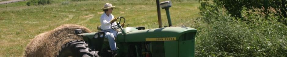 Sylvia Burgos Toftness uses an old John Deere to move 1000-lb bales of hay on her farm, Bull Brook Keep.