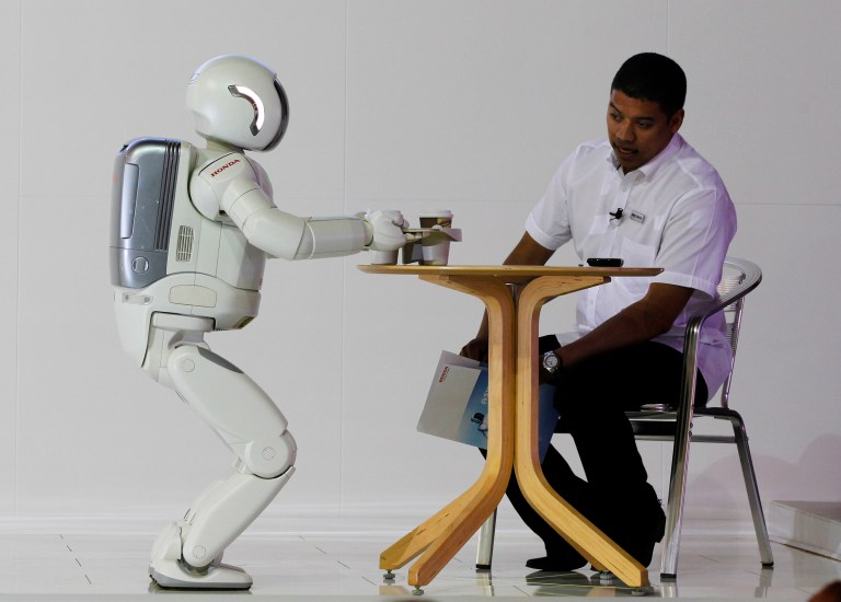 Reuters/Siphiwe Sibeko - ASIMO, a humanoid robot created by Honda Motor Company, serving tea to a guest