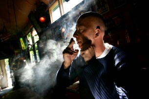 An unidentified man smokes a marijuana joint in a coffeeshop in Rotterdam in this June 14, 2005 file picture. The Dutch may well follow other European countries in banning tobacco smoking in restaurants, cafes and bars but it should still be possible to inhale cannabis pure by using a 'volcano'. Picture taken June 14, 2005. REUTERS/Jerry Lampen (NETHERLANDS) - RTR1OUJ2