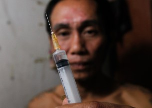Tuan Anh Nguyen, 45, holds a syringe filled with heroin in his rented room in Hanoi November 23, 2011. Tuan Anh began abusing drugs 23 years ago after being released from prison. He has since spent most of his life in prisons and rehabilitation centres. Tuan Anh earns a living by running an illegal tea stall that generates $3 to $5 of income daily. REUTERS/Kham (VIETNAM - Tags: HEALTH SOCIETY DRUGS) - RTR2UDNN