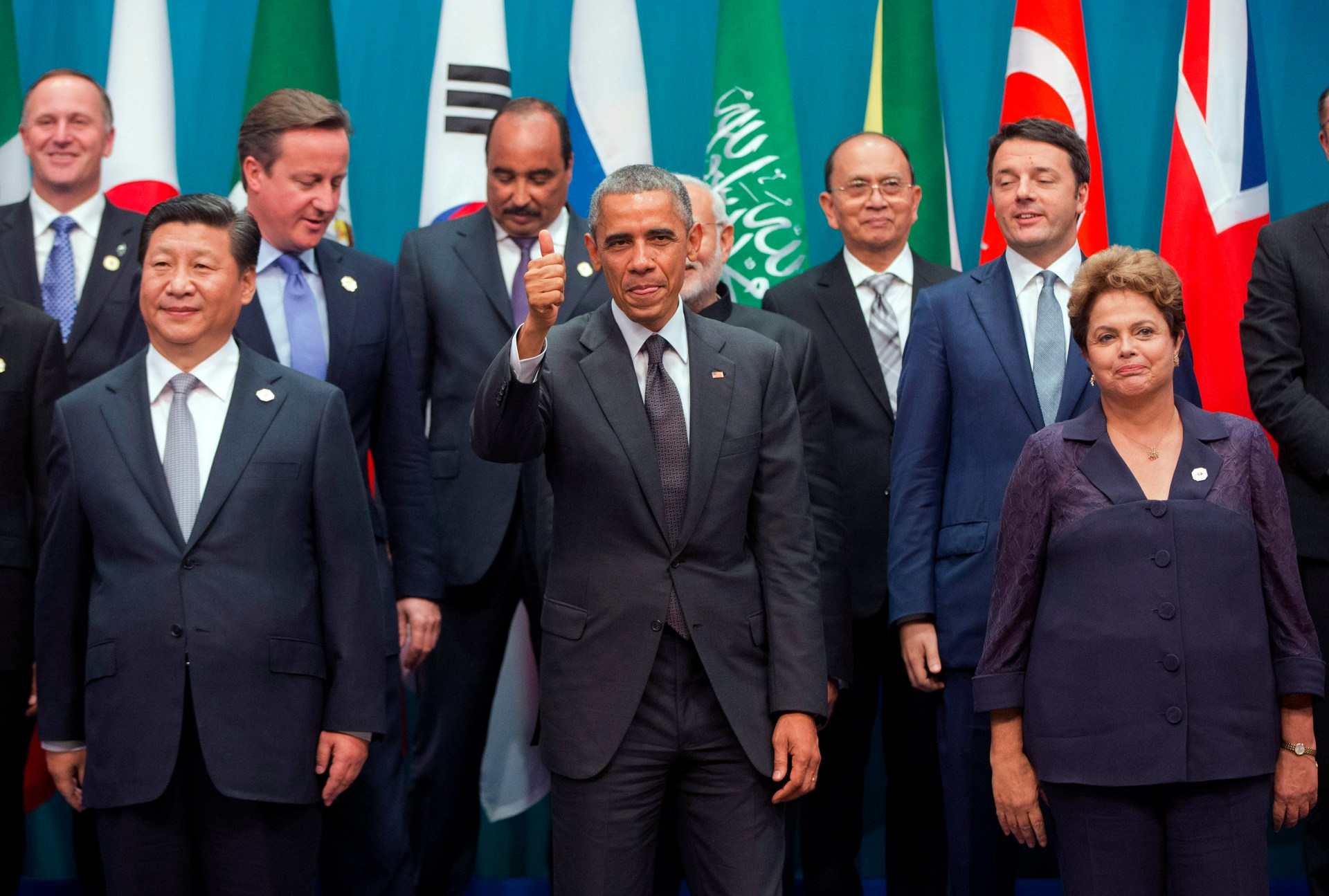 Reuters/Pablo Martinez Monsivais - U.S. President Barack Obama gives a thumbs-up to the camera as he and other leaders pose for a group photo at the G20 summit in Brisbane November 15, 2014.