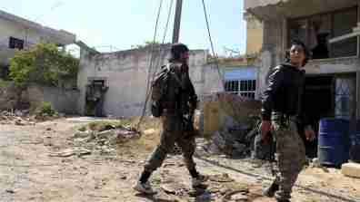 """REUTERS/Mohamad Bayoush-Fighters from a coalition of rebel groups called """"Jaish al Fateh"""", also known as """"Army of Fatah"""" (Conquest Army), walk with their weapons near Psoncol town after saying they had taken control of it, in the Idlib countryside, Syria June 6, 2015. Sunni Islamist groups have overrun Syrian army outposts and villages in western Idlib province, closing on coastal strongholds of President Bashar al Assad's government, rebels and a monitor said on Saturday."""