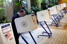 A man votes at a small, desk-style voting booth.
