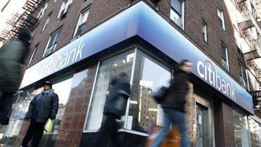 A man walking past a bank.