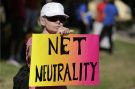 A woman holds a protest sign for net neutrality. New FCC rule making could affect internet freedom.