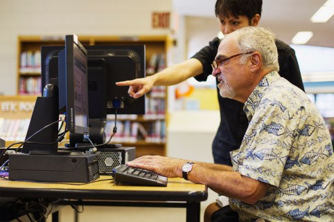 Child explains to a senior how to use a computer