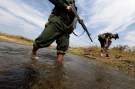 A soldier from the Kachin Independence Army (KIA) puts on his shoes as he and his comrade cross a stream towards the front line in Laiza, Kachin state, January 29, 2013. Myanmar's government started talks with top commanders of the KIA rebel group in China on February 4, 2013 to try to rescue a faltering peace process and end one of the country's bloodiest ethnic conflicts. KIA is fighting for autonomy for Kachin state within a federal Myanmar, which successive governments of the ethnically diverse country have long rejected. Picture taken January 29, 2013. REUTERS/David Johnson