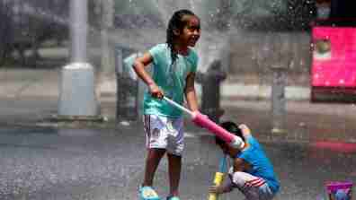 Children play in water spraying from a fire hydrant.