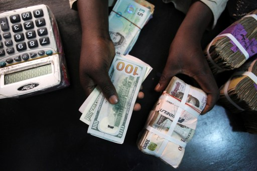 A trader changes dollars for naira at a currency exchange store in Lagos, Nigeria, February 12, 2015. REUTERS/Joe Penney/File Photo