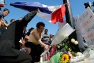 A woman places a bouquet of flower with others to pay tribute to victims near the scene where a truck ran into a crowd at high speed killing scores and injuring more who were celebrating the Bastille Day national holiday, in Nice, France, July 15, 2016. REUTERS/Pascal Rossignol