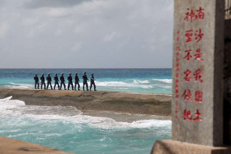 "Soldiers of China's People's Liberation Army (PLA) Navy patrol near a sign in the Spratly Islands, known in China as the Nansha Islands, February 9, 2016. The sign reads ""Nansha is our national land, sacred and inviolable."" REUTERS/Stringer/File Photo"