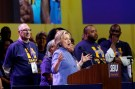 Hillary Clinton speaks at the podium of an SEIU event, joined by SEIU members in matching t-shirts.