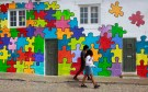People walk past a house painted in a puzzle pattern in Eiriceira village North of Lisbon August 13, 2011. Portugal still faces some tough challenges but is on track to meet this year's budget deficit goal despite a shortfall in performance so far, officials from the European Union and IMF said on Friday. REUTERS/Jose Manuel Ribeiro (PORTUGAL - Tags: POLITICS BUSINESS)