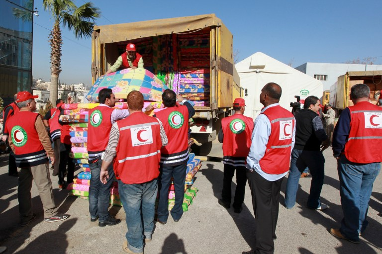 Iraqi and Jordanian Red Crescent workers load blankets and mattresses onto a truck, to deliver to Syrian refugees, in Amman February 10, 2013. About 3,000 Syrian refugee families living in Jordan received humanitarian aid from the Iraqi Red Crescent organization, in coordination with the Jordanian Red Crescent, the organisation said. REUTERS/Muhammad Hamed (JORDAN - Tags: POLITICS SOCIETY IMMIGRATION) - RTR3DKK1