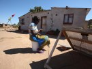 A women checks a message on her mobile phone in Epworth, east of the capital Harare, Zimbabwe
