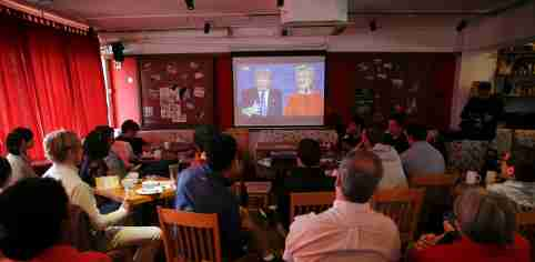 People watch a direct broadcast of the first U.S. presidential debate between Republican U.S. presidential nominee Donald Trump and Democratic U.S. presidential nominee Hillary Clinton at a cafe in Beijing, China, September 27, 2016. REUTERS/Damir Sagolj - RTSPKXI