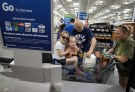 A family uses the self-checkout at the Wal-Mart owned Sam's Club in Bentonville, Arkansas June 4, 2015.  Wal-Mart will hold its annual meeting June 5, 2015.  REUTERS/Rick Wilking - RTX1F5QU