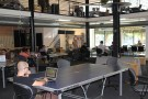 WIKIMEDIA/Msingularian-Open office space with man sitting with a laptop at a ping pong table, October 1, 2012.