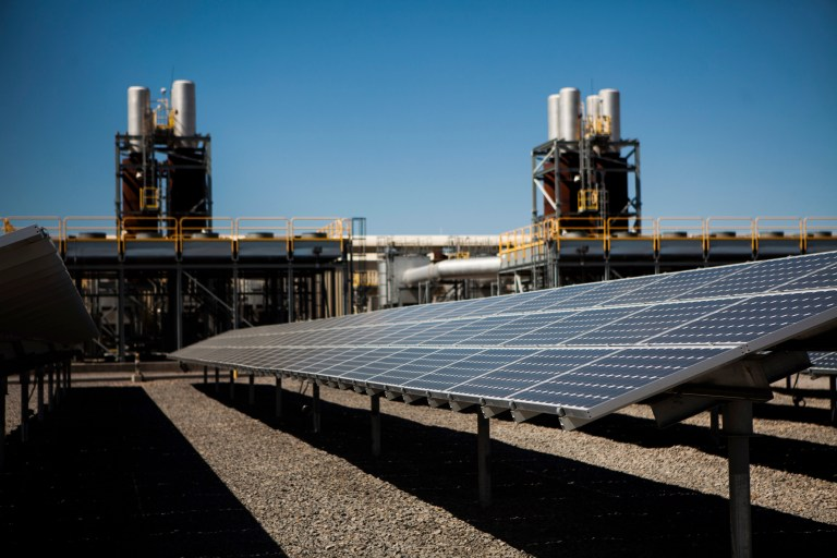 Solar panels are seen in front of a natural gas power plant at the Tahoe-Reno Industrial Center in McCarran, Nevada, September 16, 2014. This industrial site is where Elon Musk's electric car maker Tesla Motors plans to build a $5 billion factory to produce lithium ion batteries for electric cars, helped by more than $1 billion of incentives provided by Nevada. Tesla may employ 6,500 people at the new plant. In the past three years, 50 companies have moved to this area, helping cut unemployment in half and restoring some life to the town of Reno. Picture taken September 16. To match Feature USA-RENO/TESLA REUTERS/Max Whittaker (UNITED STATES - Tags: BUSINESS TRANSPORT ENERGY) - RTR48LGZ