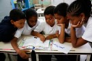 """Children read state-issued textbooks from the """"Bicentennial Collection"""" at a classroom of the Eleazar Lopez Contreras school in Caracas May 23, 2014.  Venezuela's government has published dozens of new textbooks that glorify late president Hugo Chavez and belittle his adversaries, infuriating opposition critics who call them part of a campaign to indoctrinate school children. Originally introduced in mid-2011, the textbooks have become a hot-button issue again amid a broad state-run review of the education system that some fear could boost the ruling Socialist Party's imprint on classrooms. Picture taken on May 23, 2014. REUTERS/Carlos Garcia Rawlins (VENEZUELA - Tags: EDUCATION POLITICS) - RTR3RVIS"""