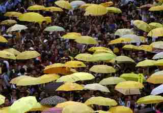 "Pro-democracy protesters carrying yellow umbrellas, symbol of the Occupy Central civil disobedience movement, gather outside government headquarters in Hong Kong, China September 28, 2015. Monday marks the first anniversary of the Occupy Central or ""umbrella"" movement, demanding universal suffrage in the territory. REUTERS/Bobby Yip - RTX1SU40"