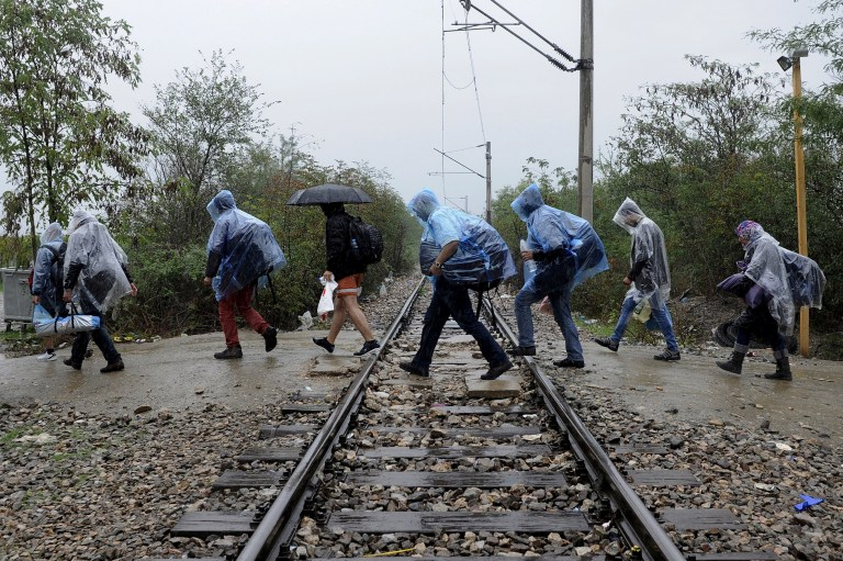 A group of Syrian refugees wearing plastic raincoats to protect from heavy rainfall, walk across a railway line into Macedonia near the Greek village of Idomeni, September 26, 2015. A record number of at least 430,000 refugees and migrants have taken rickety boats across the Mediterranean to Europe this year, 309,000 via Greece, according to International Organization for Migration figures. REUTERS/Alexandros Avramidis TPX IMAGES OF THE DAY - RTX1SLYV