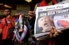"""A newspaper seller holds a newspaper with an article about the election of U.S. Republican candidate Donald Trump as president, in Jakarta, Indonesia, November 10, 2016. The headline reads """"Why Trump?""""REUTERS/Beawiharta - RTX2SXWU"""