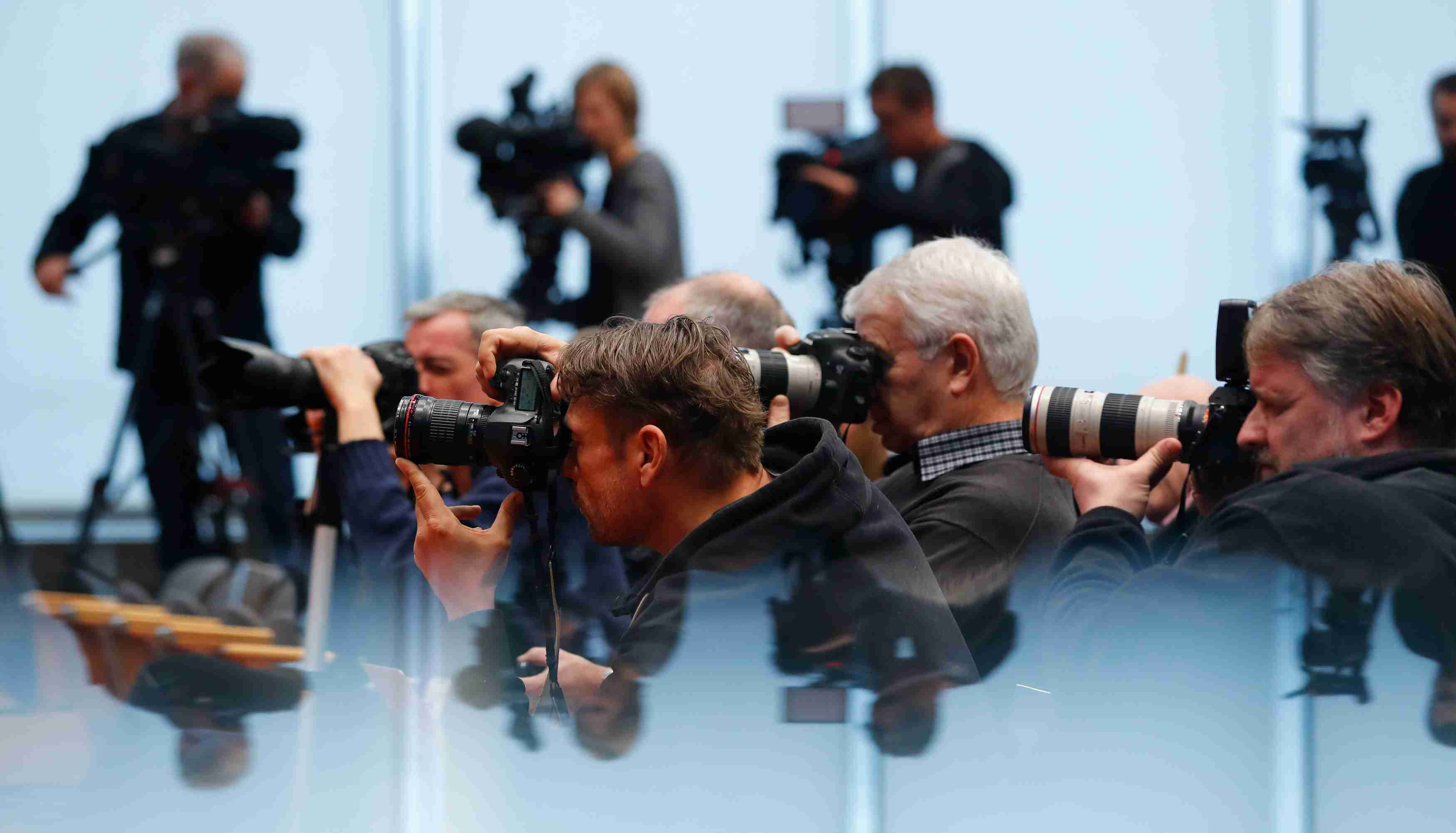 Journalists take pictures during a news conference