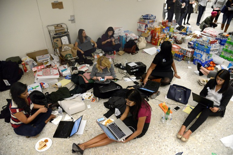 Lawyers and legal assistants network and use social media in the baggage claim area, amid supplies of pizza, water and other food, at Dulles International Airport, aiding passengers who have arrived and encounter problems because of Donald Trump's travel ban to the United States, in Chantilly, Virginia, in suburban Washington, U.S., January 29, 2017. REUTERS/Mike Theiler - RTSXZ6R