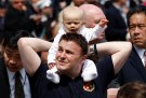 A man carries a baby as they wait for Pope Benedict XVI to celebrate Mass at Yankee Stadium in New York, April 20, 2008.     REUTERS/Mike Segar (UNITED STATES) - RTR1ZPJI