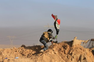A member of the federal police forces puts up an Iraqi flag at a position during a battle with Islamic State militants in south of Mosul