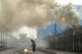 A labourer works at a coking plant in Changzhi, north China's Shanxi province, July 7, 2007. Starting off in Sydney on Saturday and travelling west around the world, the Live Earth concerts, planned for this weekend, are expected to attract more than a million people to raise awareness of global warming and environmental issues like climate change. REUTERS/Stringer (CHINA) CHINA OUT - RTR1RJUT