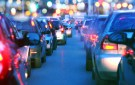 iStock Images. Driving a car in a a city with a traffic jam at night, proceeding slow in a line of cars with red tail lights during the rush hour. view from inside the car. Blurred streets lights on the background. Dusk, blue skylight.