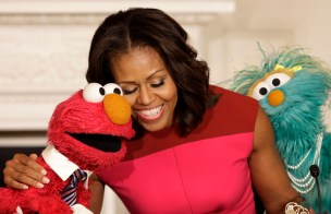 U.S. first lady Michelle Obama hugs PBS Sesame Street characters Elmo and Rosita after delivering remarks on marketing healthier foods to children at the White House in Washington