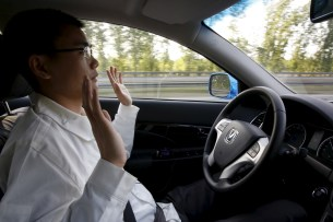 Li Zengwen, a development engineer at Changan Automobile, lifts his hands off the steering wheel as the car is on self-driving mode during a test drive on a highway in Beijing