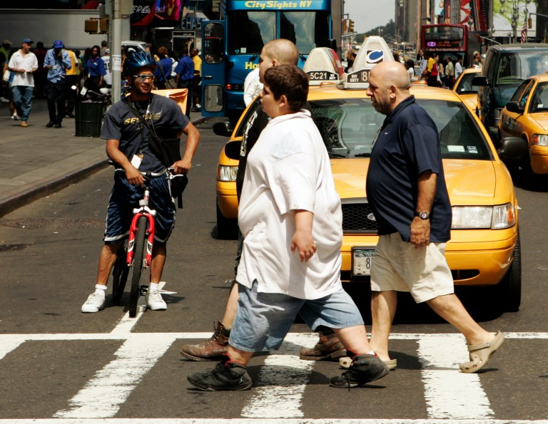 A cyclist smiles as he watches pedestrians walk across a street near Times Square in New York