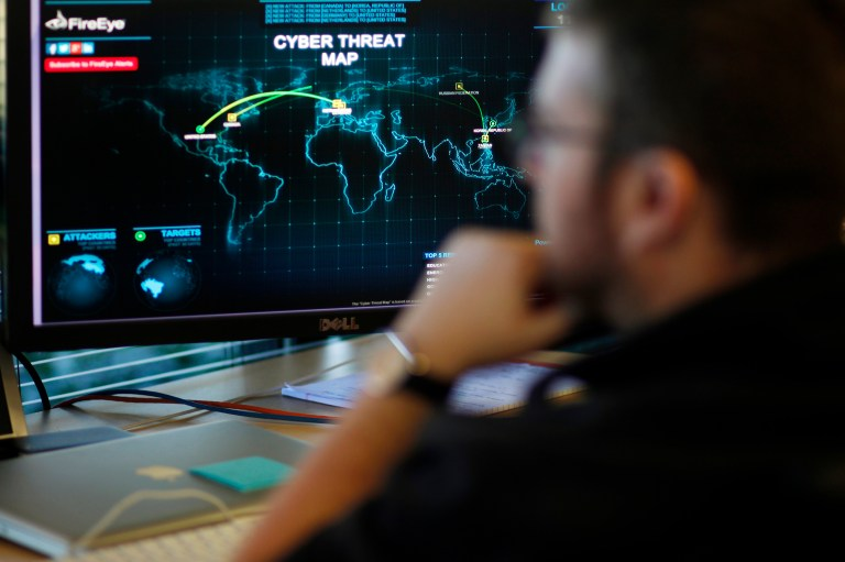 A FireEye information analyst works in front of a screen showing a near real-time map tracking cyber threats at the FireEye office in Milpitas, California, December 29, 2014. FireEye is the security firm hired by Sony to investigate last month's cyberattack against Sony Pictures. Picture taken December 29. REUTERS/Beck Diefenbach (UNITED STATES - Tags: BUSINESS SCIENCE TECHNOLOGY CRIME LAW) - RTR4JTQC