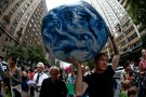 A man carries an inflatable earth balloon along West 72nd Street during the People's Climate March in New York, September 21, 2014. An international day of action on climate change brought hundreds of thousands of people onto the streets of New York City on Sunday, easily exceeding organizers' hopes for the largest protest on the issue in history. Organizers estimated that some 310,000 people, including United Nations Secretary-General Ban Ki-moon, former U.S. Vice President Al Gore, actor Leonardo DiCaprio and elected officials from the United States and abroad joined the People's Climate March, ahead of Tuesday's United Nations hosted summit in the city to discuss reducing carbon emissions that threaten the environment.  REUTERS/Mike Segar   (UNITED STATES - Tags: POLITICS CIVIL UNREST ENVIRONMENT) - RTR475E0
