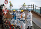 Workers, wearing protective suits and masks, are seen near the No. 3 and No.4 reactor buildings at Tokyo Electric Power Co's (TEPCO) tsunami-crippled Fukushima Daiichi nuclear power plant in Okuma town, Fukushima prefecture, Japan February 10, 2016. REUTERS/Toru Hanai - RTX26AMM