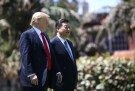 President Donald Trump and China's President Xi Jinping walk along the front patio of the Mar-a-Lago estate.