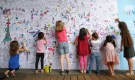 "Children colour a map of Paris on a wall as ""Paris Plages"" (Paris Beach) opens along the banks of River Seine in Paris, France, July 20, 2015. The beach, in the heart of the French capital, includes stretches of imported sand and various free sporting activities for the public. Paris Plages runs during the summer holiday season from July 20 until August 16.     REUTERS/Charles Platiau - RTX1L2SO"