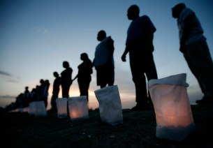 New Orleans residents stand during a candlelight ceremony dedicated to the victims and survivors of Hurricane Katrina on the levee in Orleans Parish August 28, 2006, nearly a year after the hurricane struck.