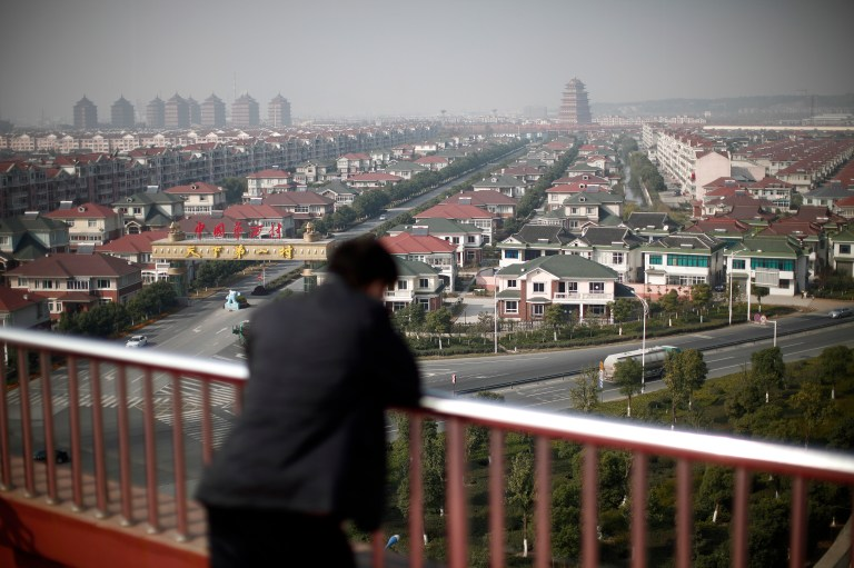 A man watches the Huaxi village, at Jiangsu province.