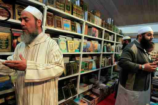 Sheikh Chemseddine Bouroubi (L), a well-known imam who follows a traditional Algerian school of Islam, reads a religious book at a Salafist stand during the 15th International Book Fair (SILA) in Algiers October 29, 2010. Algeria is cracking down on imports of books preaching the ultra-conservative Salafist branch of Islam, officials and industry insiders say, in a step aimed at reining in the ideology's growing influence. Salafism is a school of Islam that has its roots in Saudi Arabia and emphasises religious purity. Its followers reject the trappings of modern life, including music, Western styles of dress and taking part in politics. Picture taken October 29, 2010. To match Feature ALGERIA-RELIGION/BOOKS REUTERS/Zohra Bensemra (ALGERIA - Tags: EDUCATION SOCIETY RELIGION) - RTXV0GL